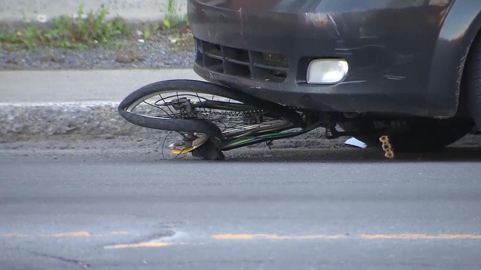 Le vélo est écrasé sous le devant de la voiture.