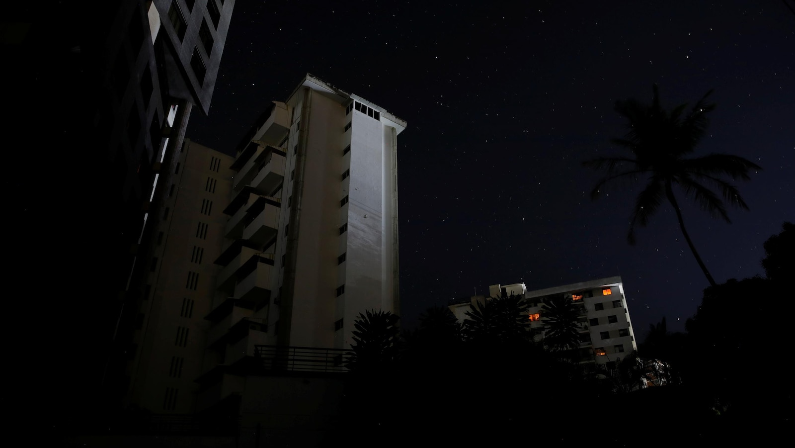 Des immeubles d'habitation sont dans le noir. De faibles lueurs apparaissent à seulement quatre fenêtres.
