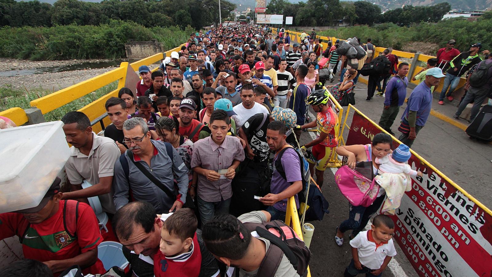 Une longue file de personnes attend sur le pont.