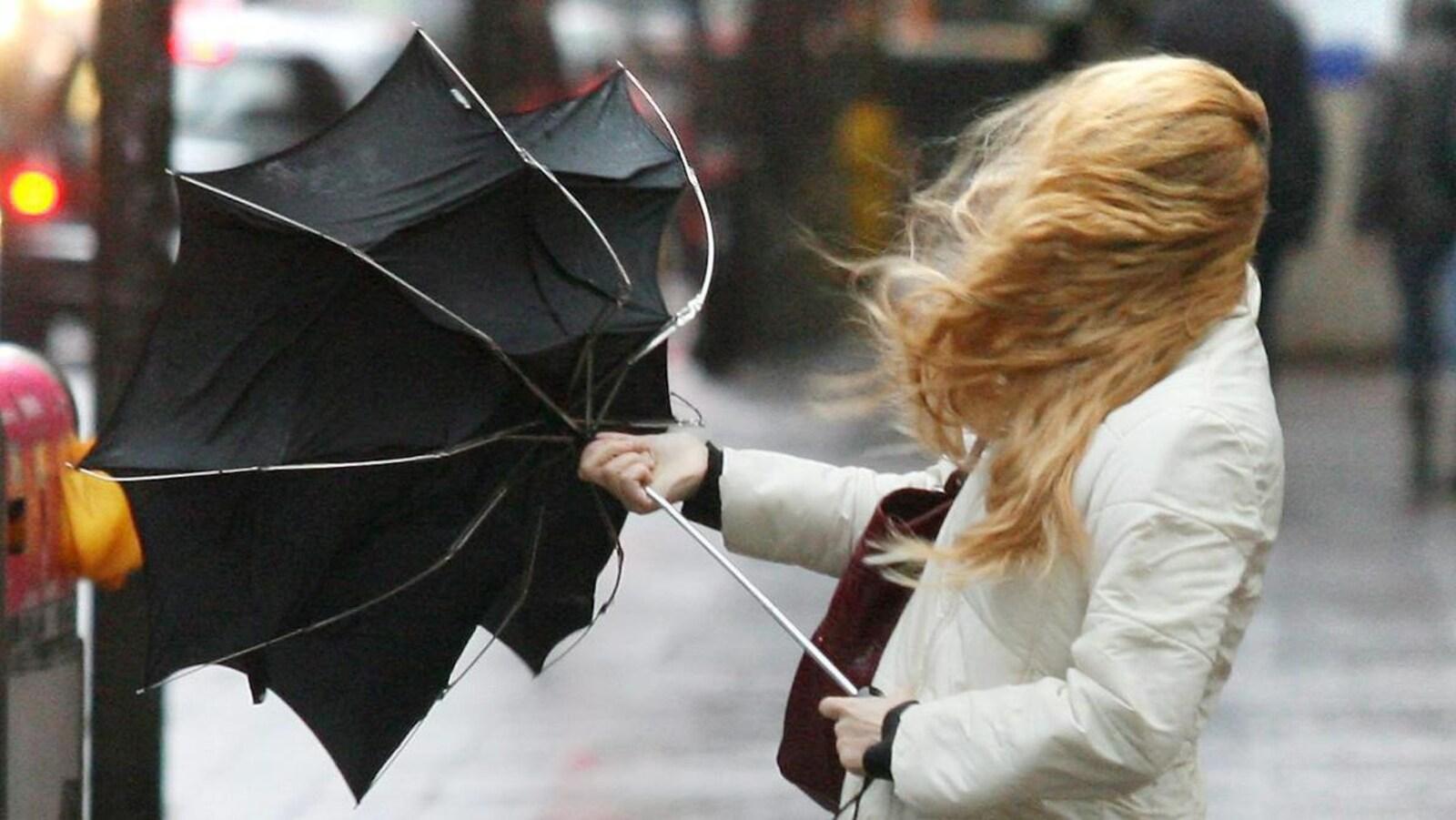 Une femme aux cheveux emportés par le vent a du mal à tenir son parapluie.