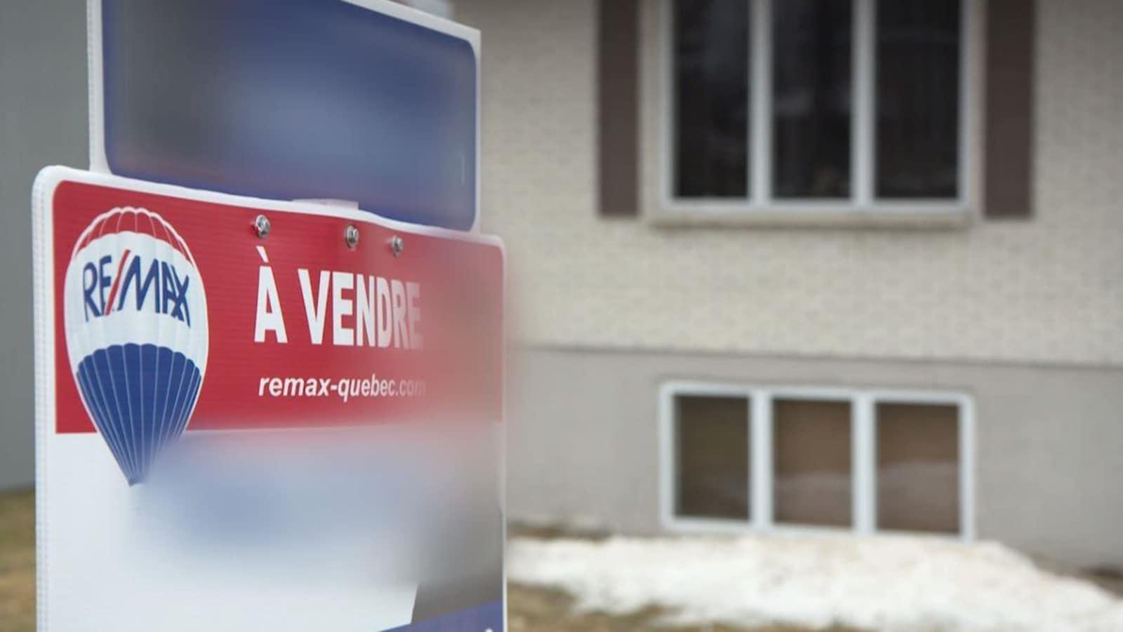 Une affiche À vendre devant un bungalow
