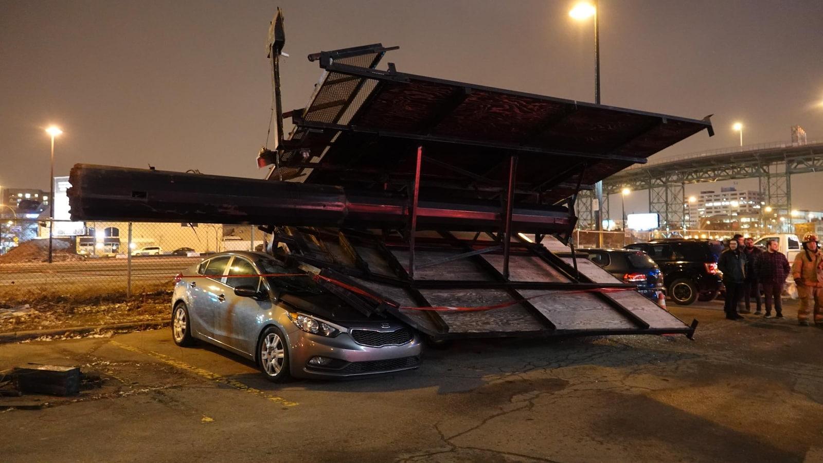 Des véhicules écrasés par la chute d'un panneau d'affichage.