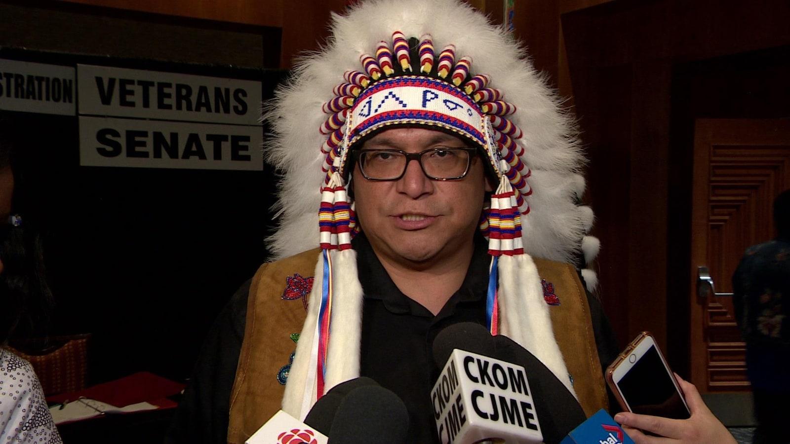 L'homme porte un couvre-chef traditionnel lors d'un point de presse.