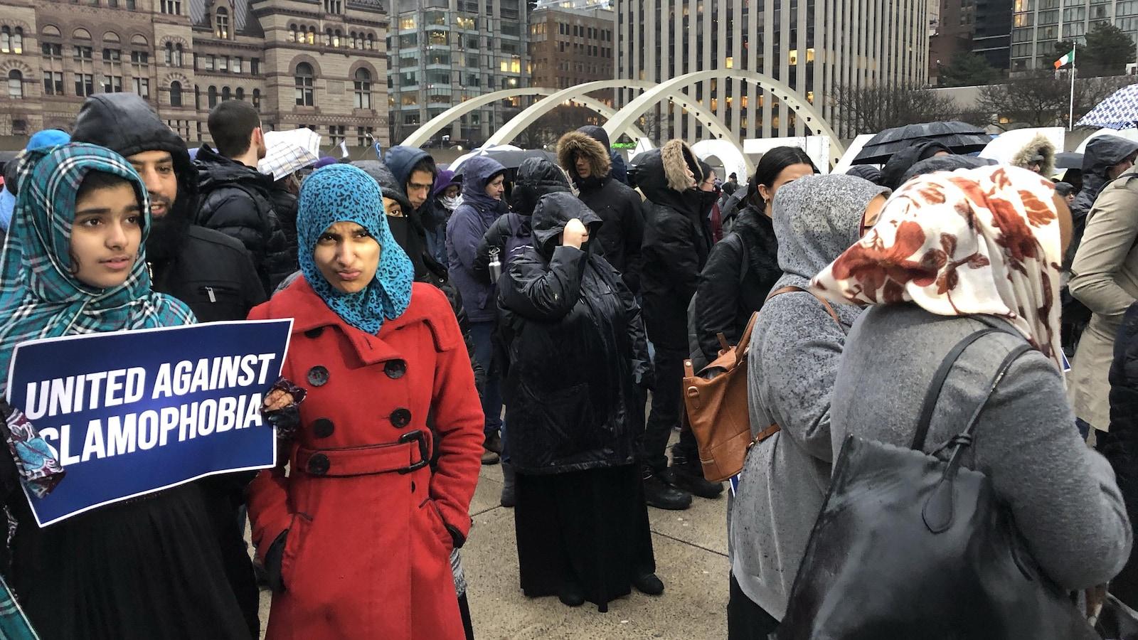 Une foule de personnes réunies devant l'hôtel de ville, dont une femme au premier plan qui tiennent une pancarte avec écrit « unis contre l'islamophobie ».