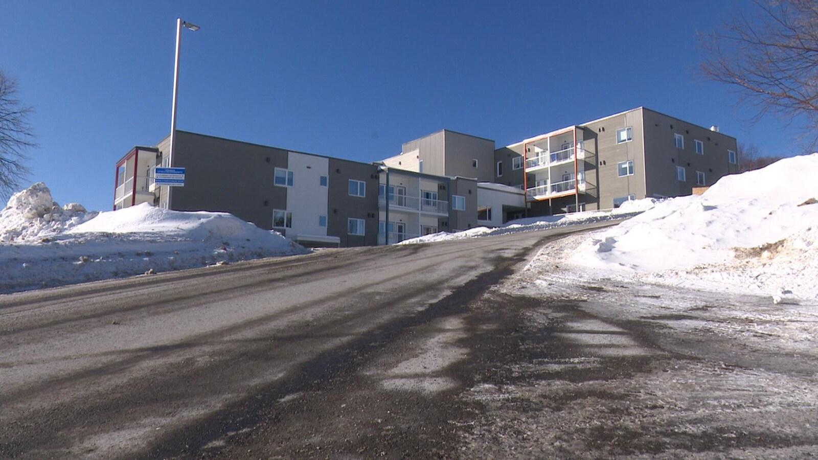 Le bâtiment gris et blanc est situé en haut d'une côte, à Gaspé.