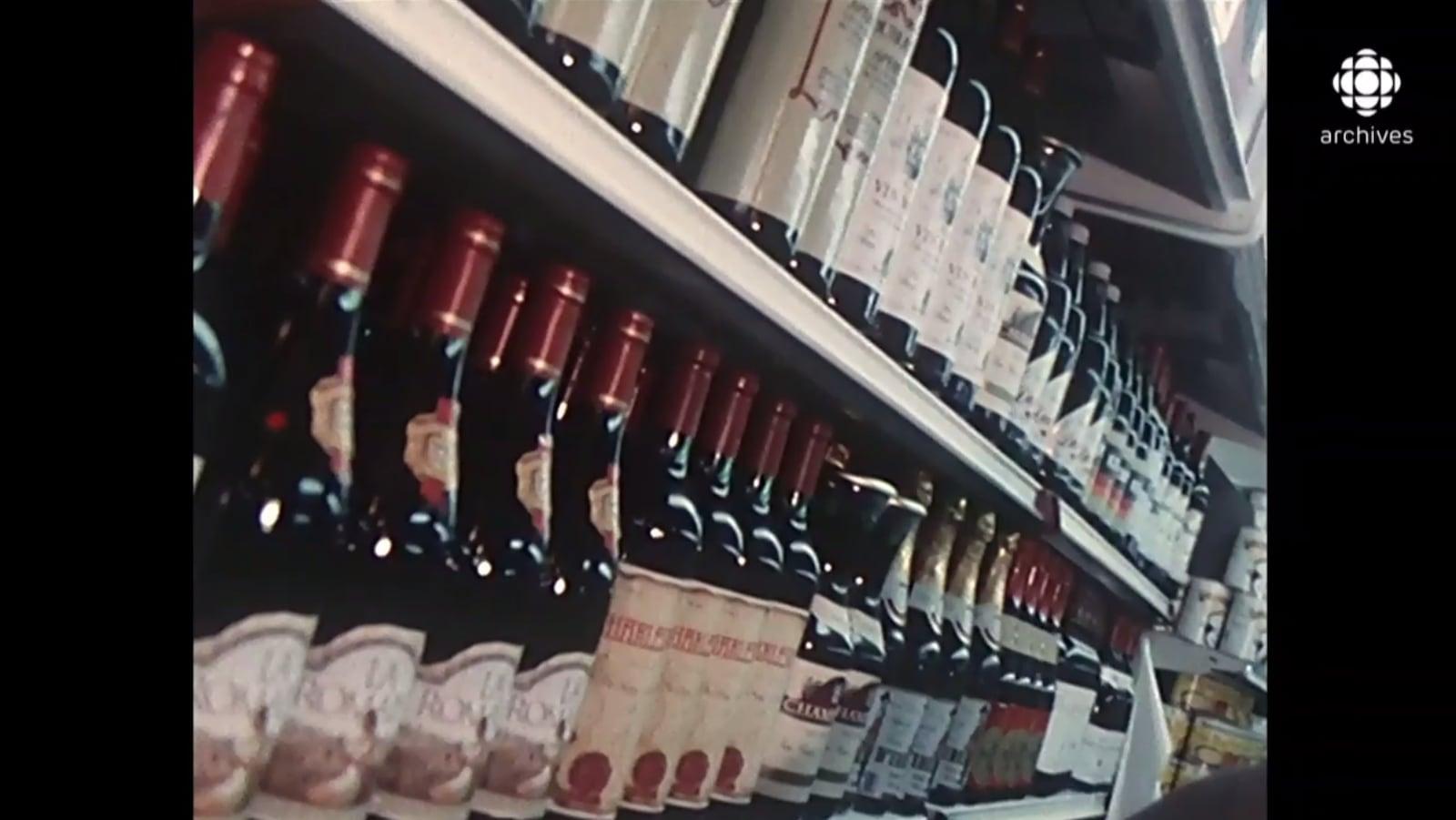 Des bouteilles de vin sont alignées sur plusieurs étagères d'une épicerie.