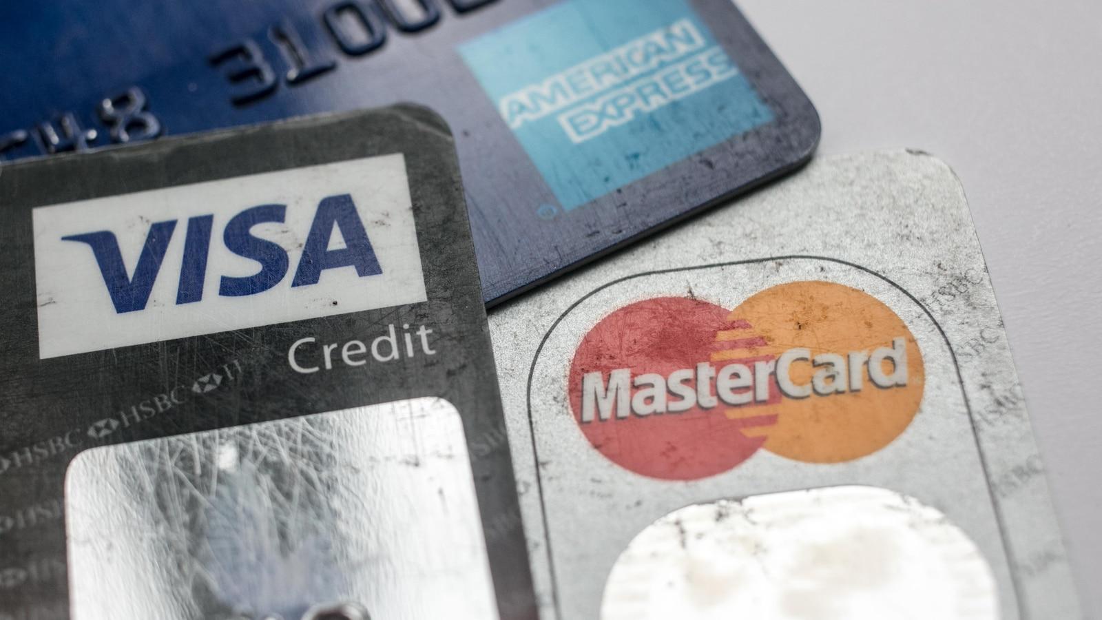 Trois cartes sur lesquelles on peut lire Visa, MasterCard et American Express sont photographiées sur une table. Elles sont vues de très près.