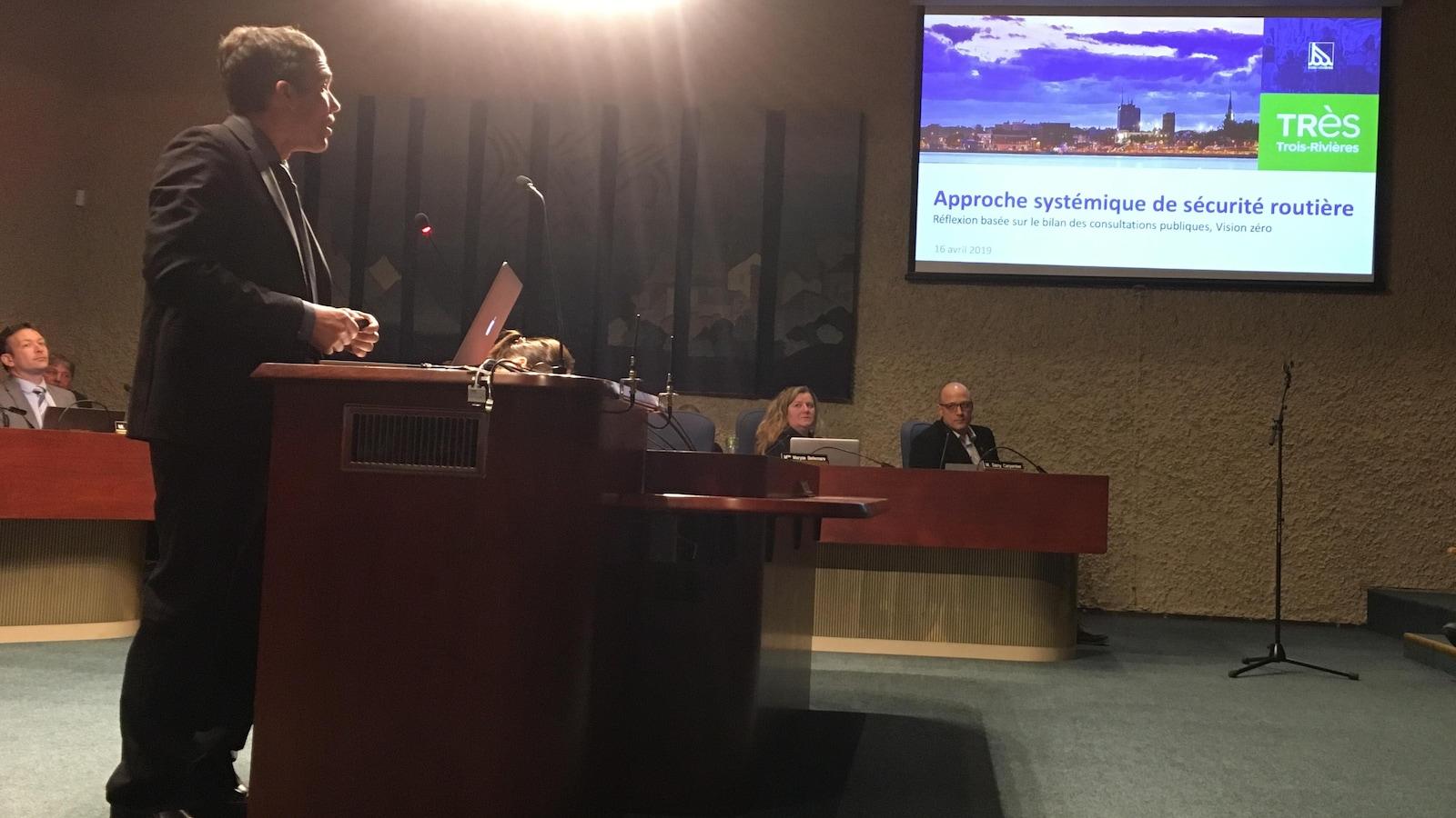 Un homme se tient derrière un bureau, il fait une présentation avec des images projetées sur une toile dans une salle de conseil municipal.