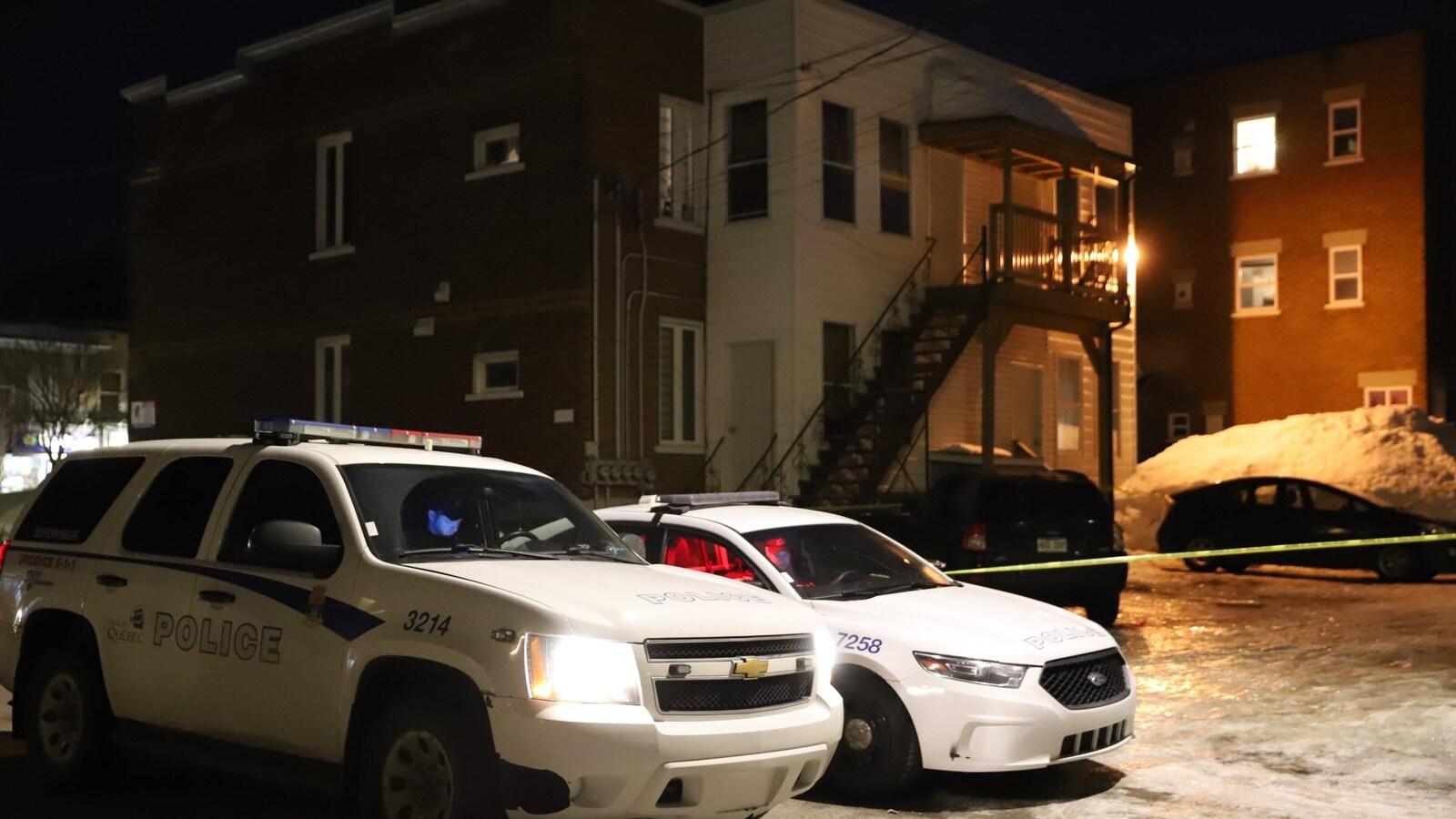 Deux véhicules de police devant un immeuble résidentiel du quartier Limoilou.