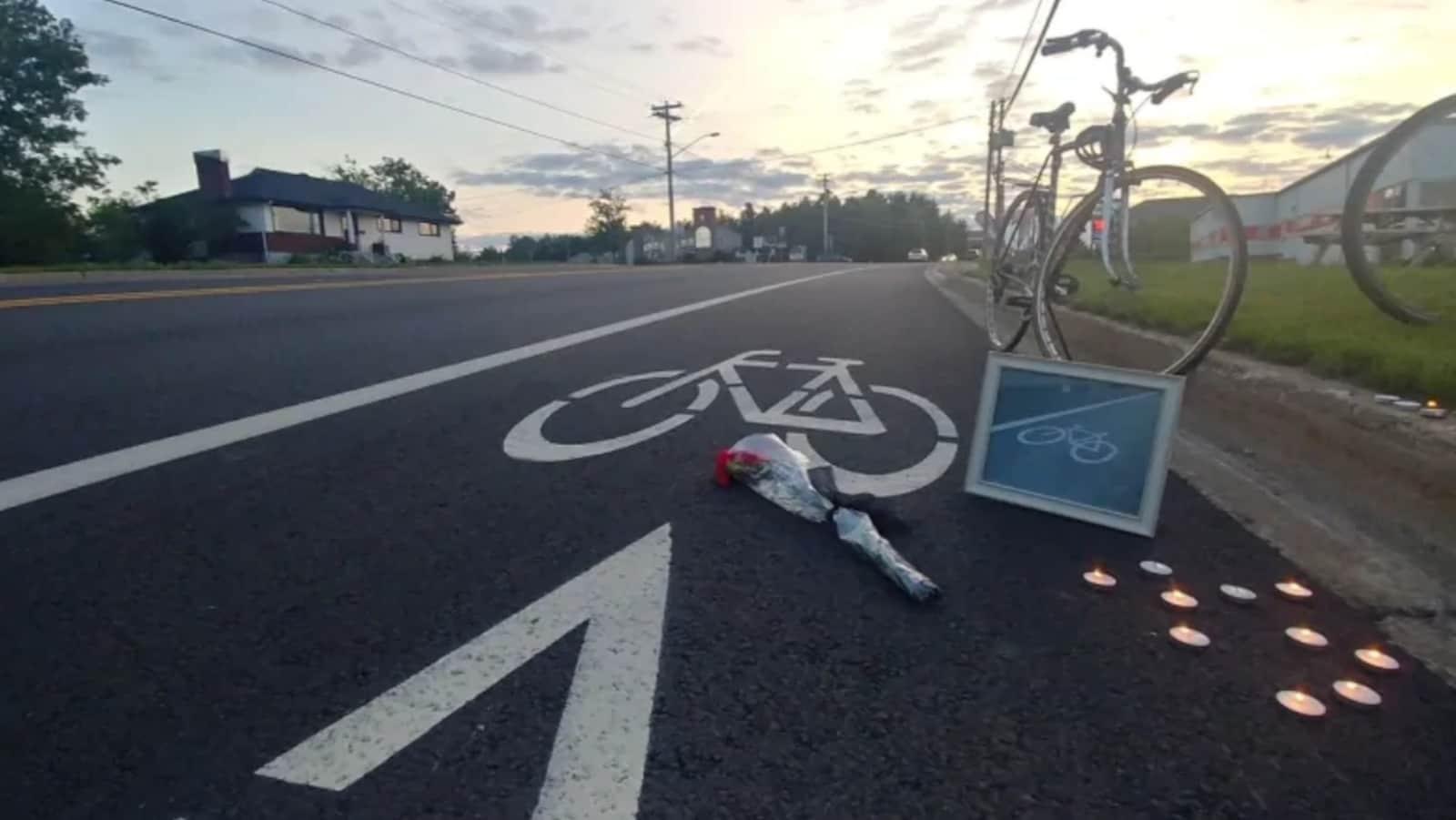 Un vélo, des bougies et des fleurs ont été posés près de la voie cyclable.