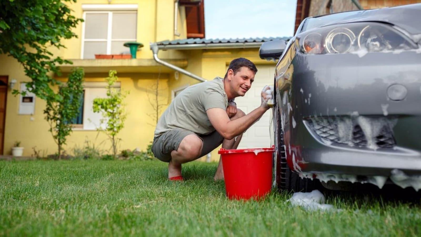 Un homme nettoie son véhicule avec une éponge, un seau d'eau et du savon.