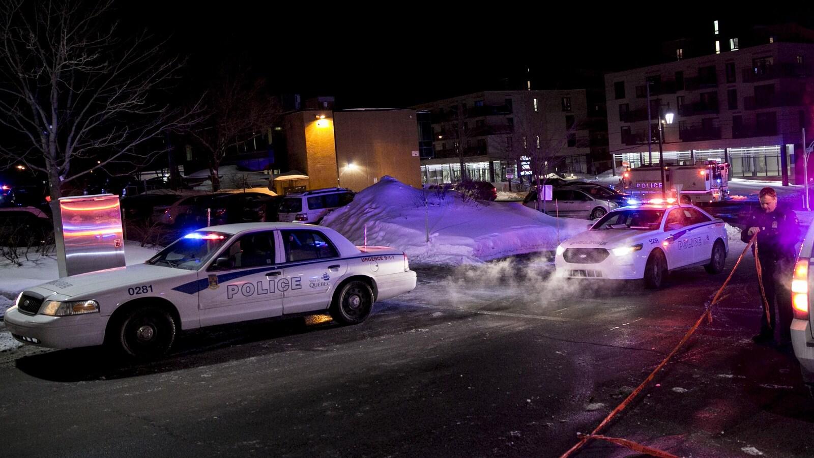 Des voitures du SPVQ stationnées aux abords du Centre culturel islamique de Québec le 29 janvier 2017. Un policier met en place un périmètre de sécurité à l'aide d'un ruban rouge.