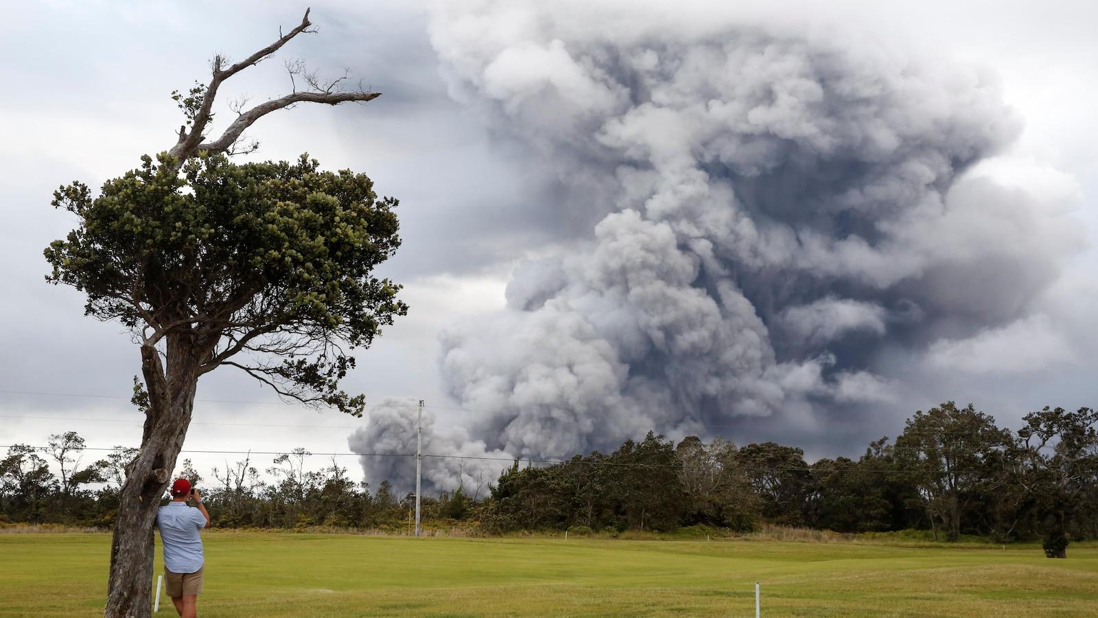 Un homme regarde au loin les éruptions du volcan Kilauea, qui assombrit le ciel de fumée.