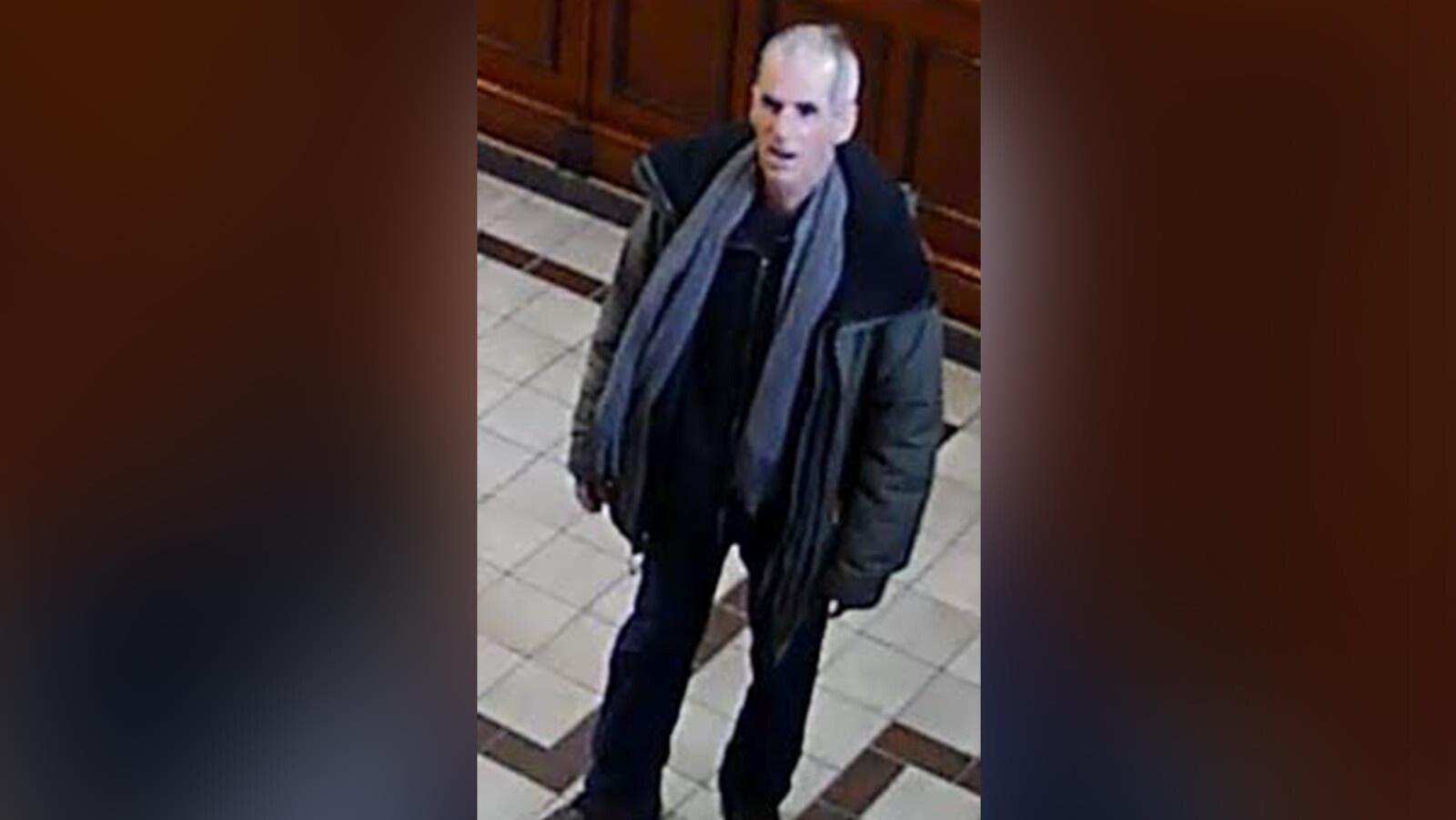 Le suspect portant un foulard gris, des pantalons noirs et un manteau vert.