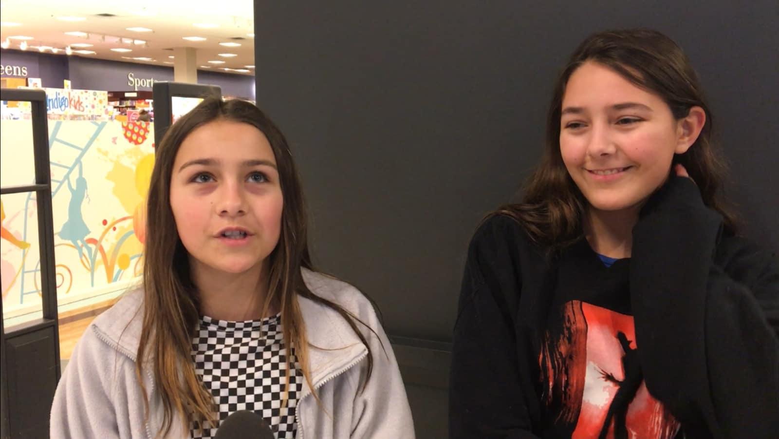 Deux jeunes filles se tiennent devant l'entrée d'un magasin, la plus jeune des deux soeurs regarde vers le haut, l'air pensive, et la plus vieille, à gauche, tient son cou en souriant, l'air gênée.