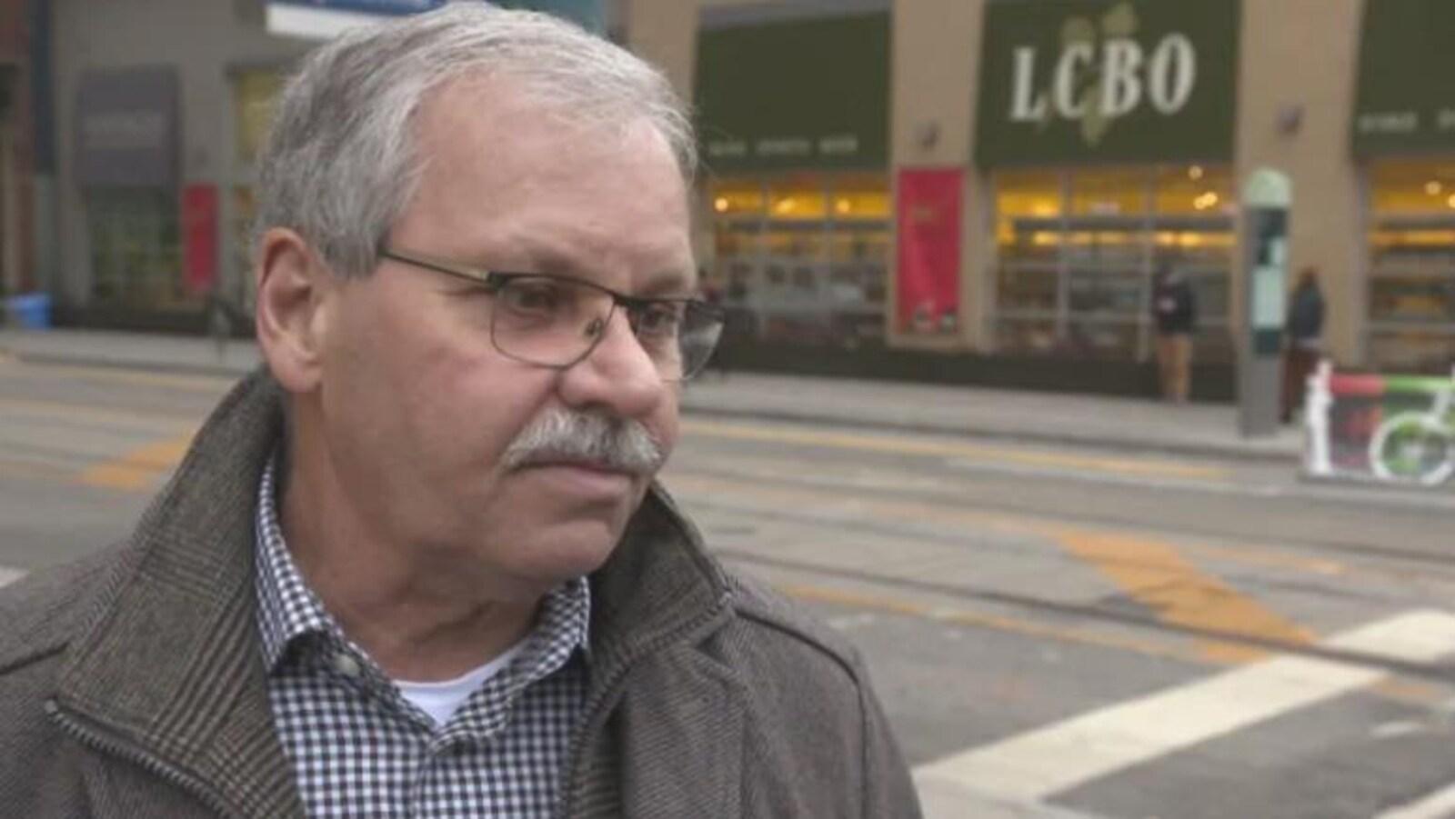 Le président du Syndicat des employés de la fonction publique de l'Ontario, Warren Smokey Thomas porte des lunettes et une moustache grise, des cheveux gris, il est dehors devant une succursale LCBO