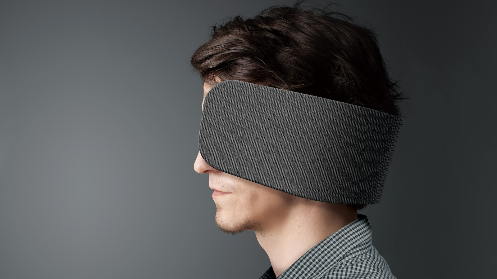Une photo montrant un homme qui porte les écouteurs Wear Space, qui ressemblent à de grosses œillères.