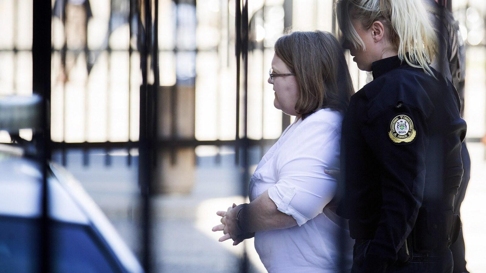 Photo de Wettlaufer qui est suivie par une policière alors qu'elle se dirige vers le tribunal.