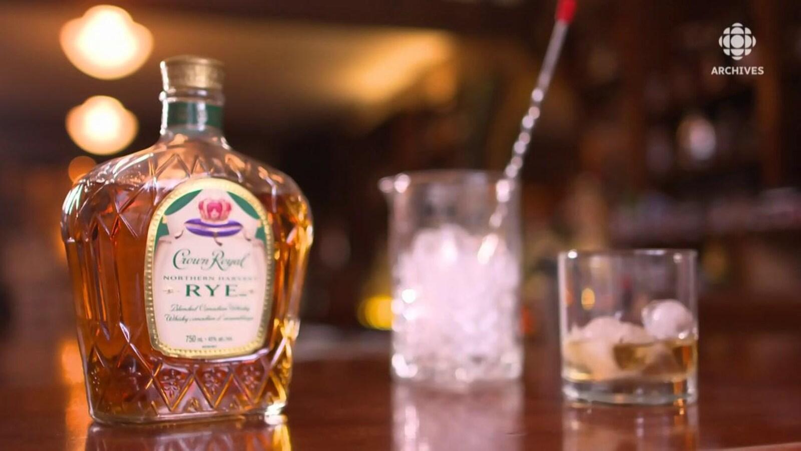 Bouteille de whisky canadien Crown Royal avec un verre et un seau de glace.