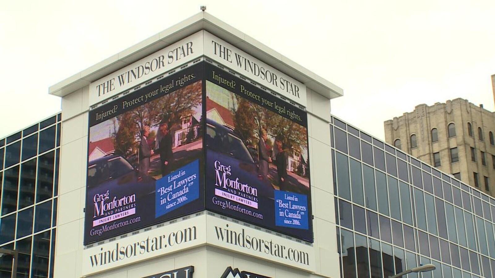 Des écrans publicitaires sont placés sur la façade de l'immeuble, sous l'enseigne The Windsor Star.