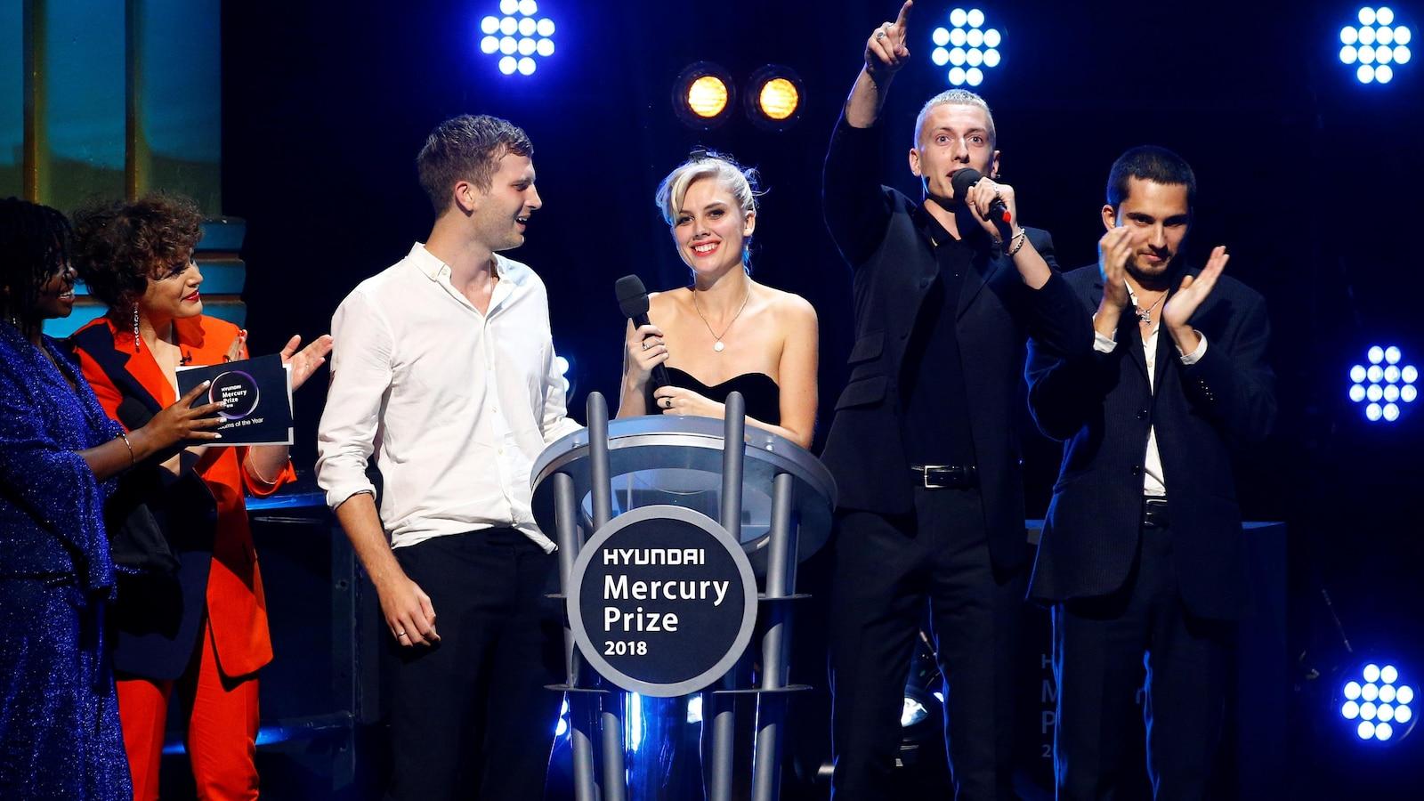 Six personnes sont sur scène dont les quatre membres du groupe qui sourient, applaudissent et lèvent la main.