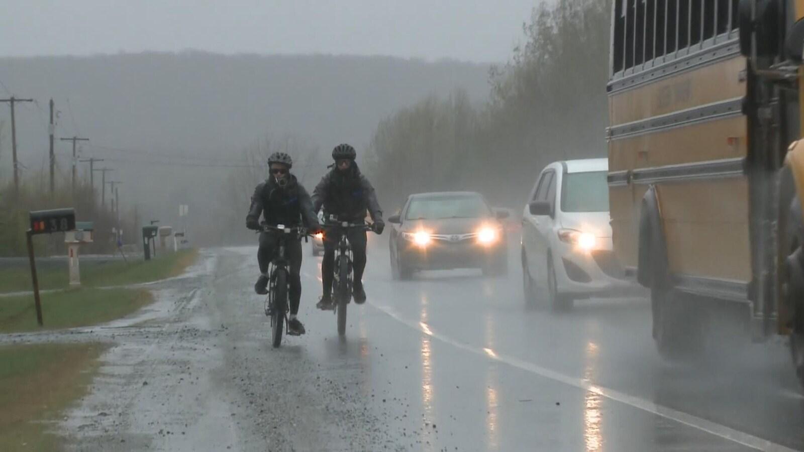 Le périple de Josué Simard-Lebrun et Xavier McConnell a commencé vendredi sous la pluie et dans le froid. On les voit ici rouler sur le bord de la route, complètement trempés