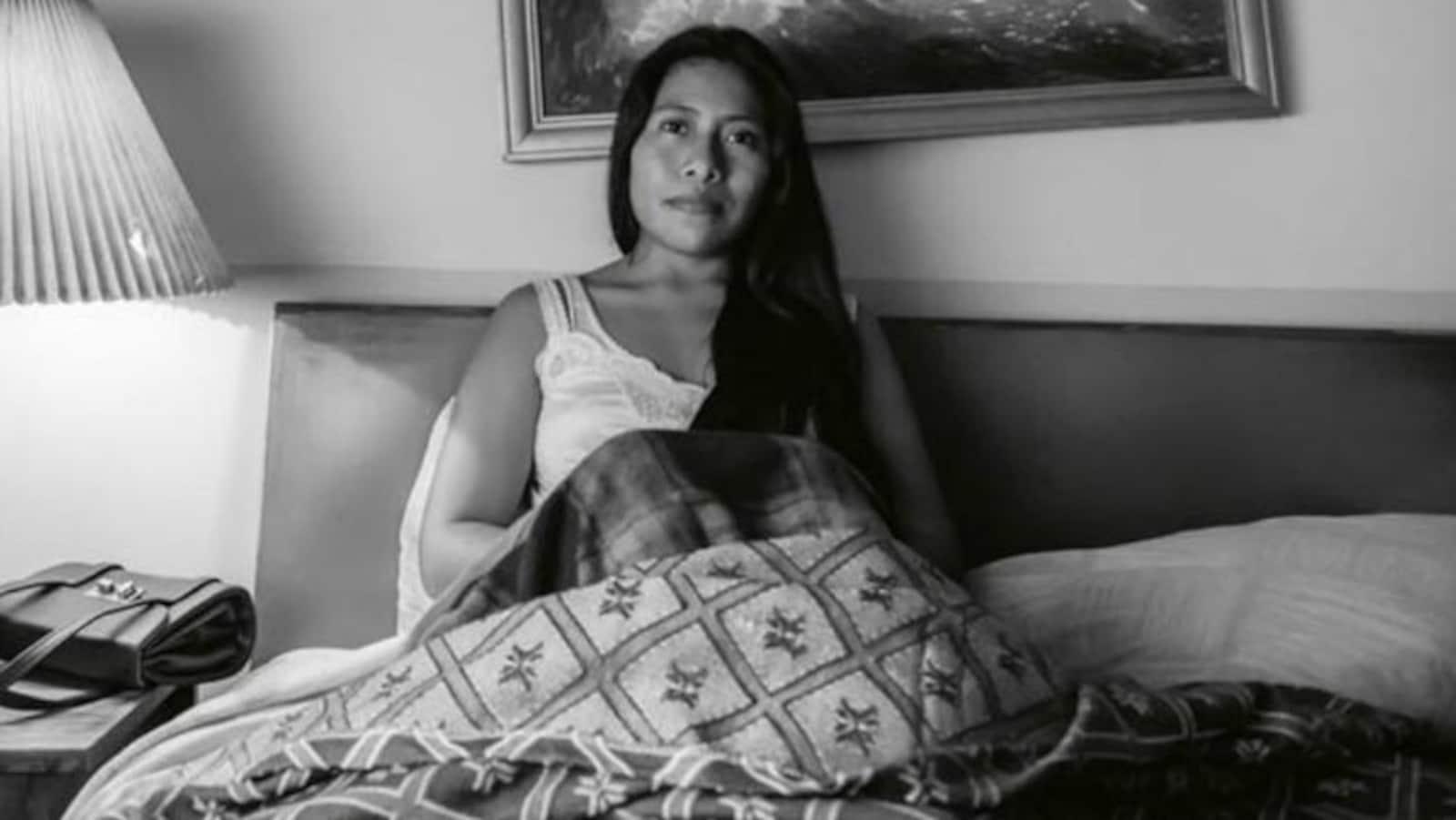 Une femme aux cheveux longs est assise dans son lit, et son regard fixe la caméra. L'image, issue du film Roma, est en noir et blanc.