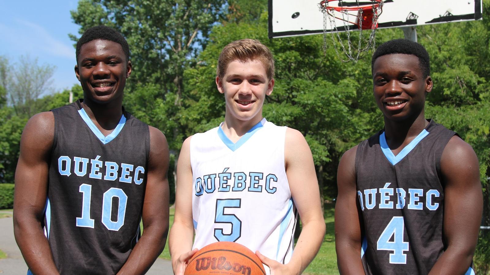 Yannice Nlend, Eldrick Rivard et Yve Nsanzinshuti prennent la pose sur un terrain de basketball extérieur. Eldrick tient un ballon entre les mains. Les trois joueurs portent une tenue de basketball aux couleurs de l'équipe du Québec.