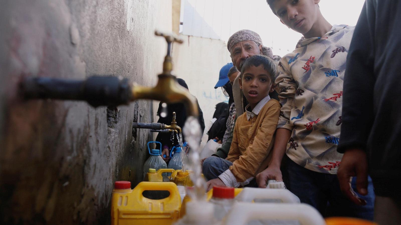 Adultes et enfants remplissent des bouteilles d'eau à des robinets installés à l'extérieur d'un bâtiment.