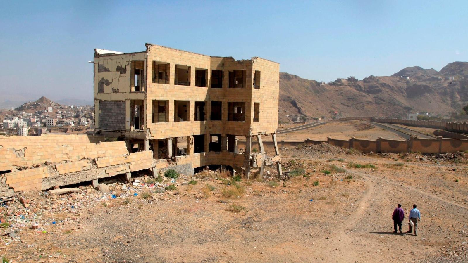 Deux personnes marchent non loin d'une école détruite par la guerre, dans le sud-ouest du Yémen.