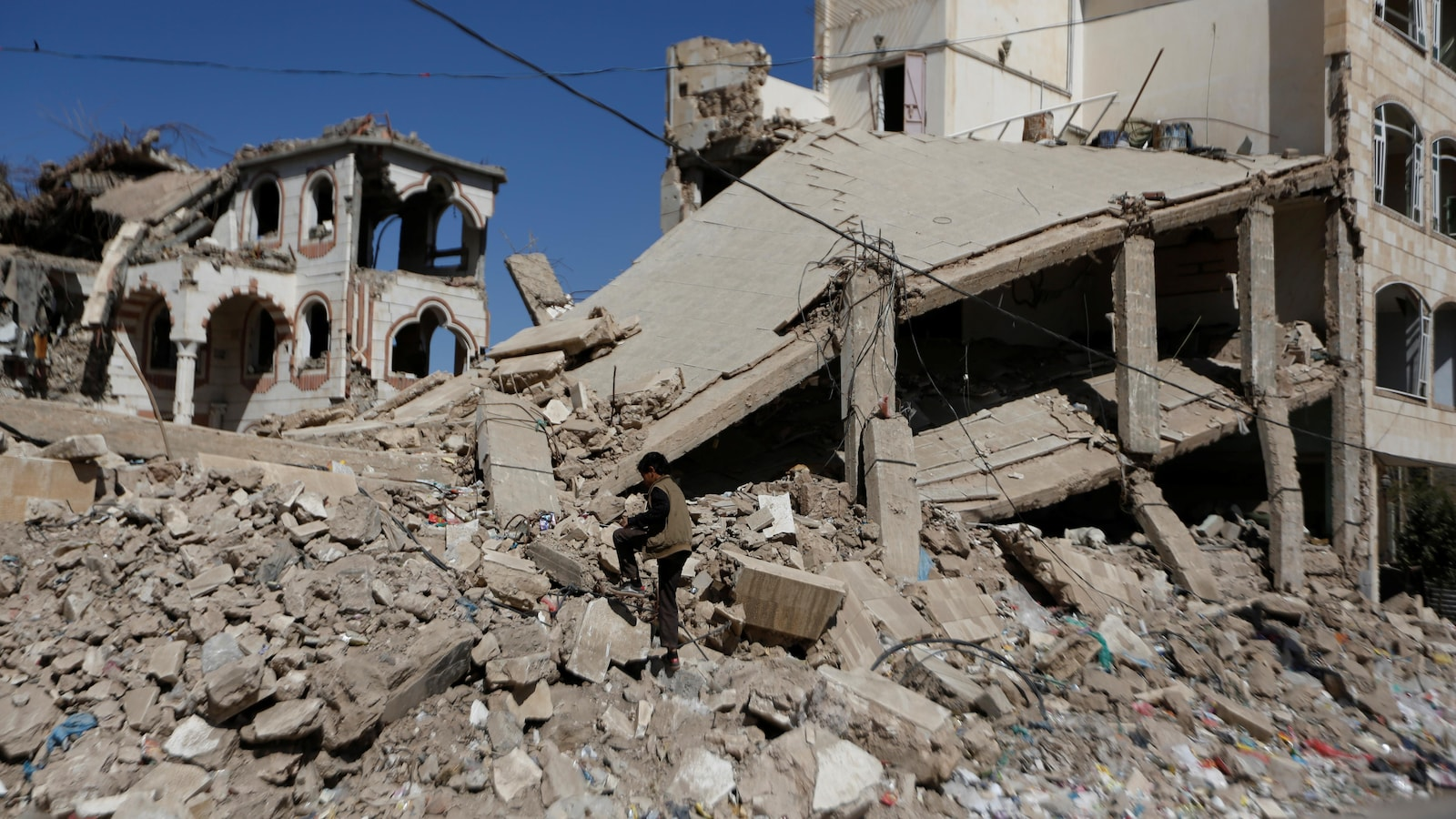 Un garçon marche sur les ruines d'un bâtiment, à Sanaa.
