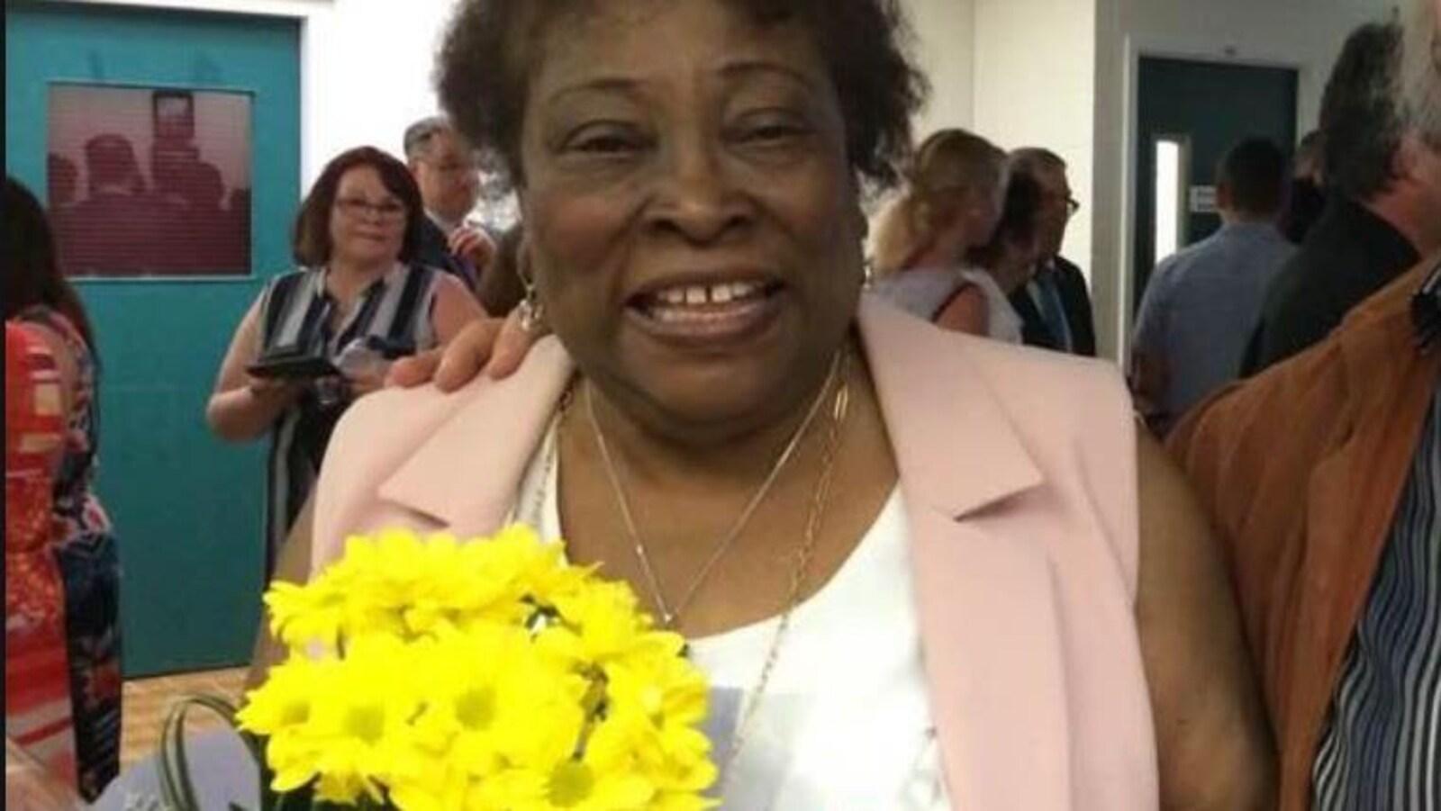 Yolette Lévy, un boquet de fleurs à la main.