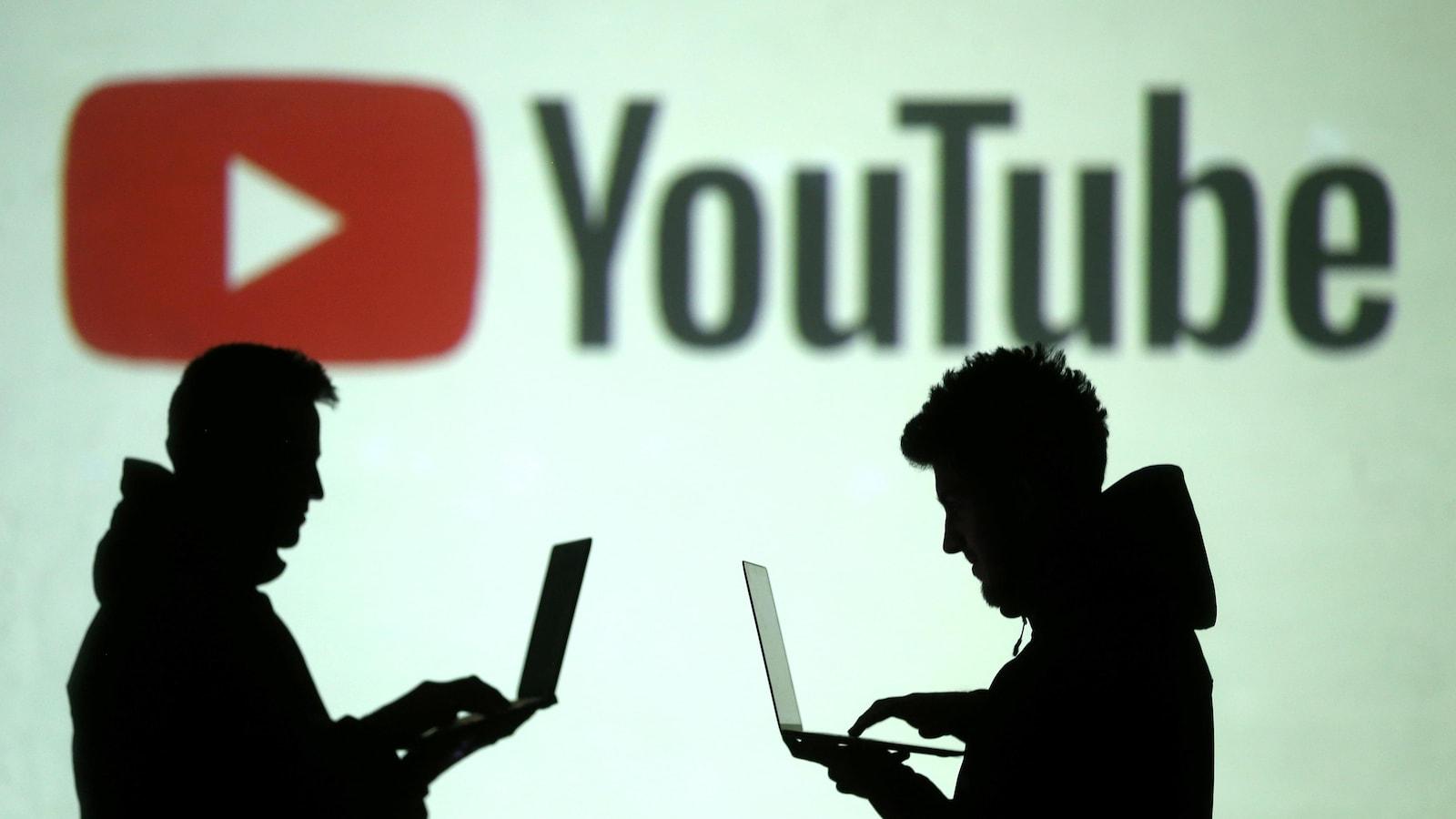 Des silhouettes de personnes utilisant des ordinateurs portables sont visibles devant un immense logo de l'entreprise YouTube.
