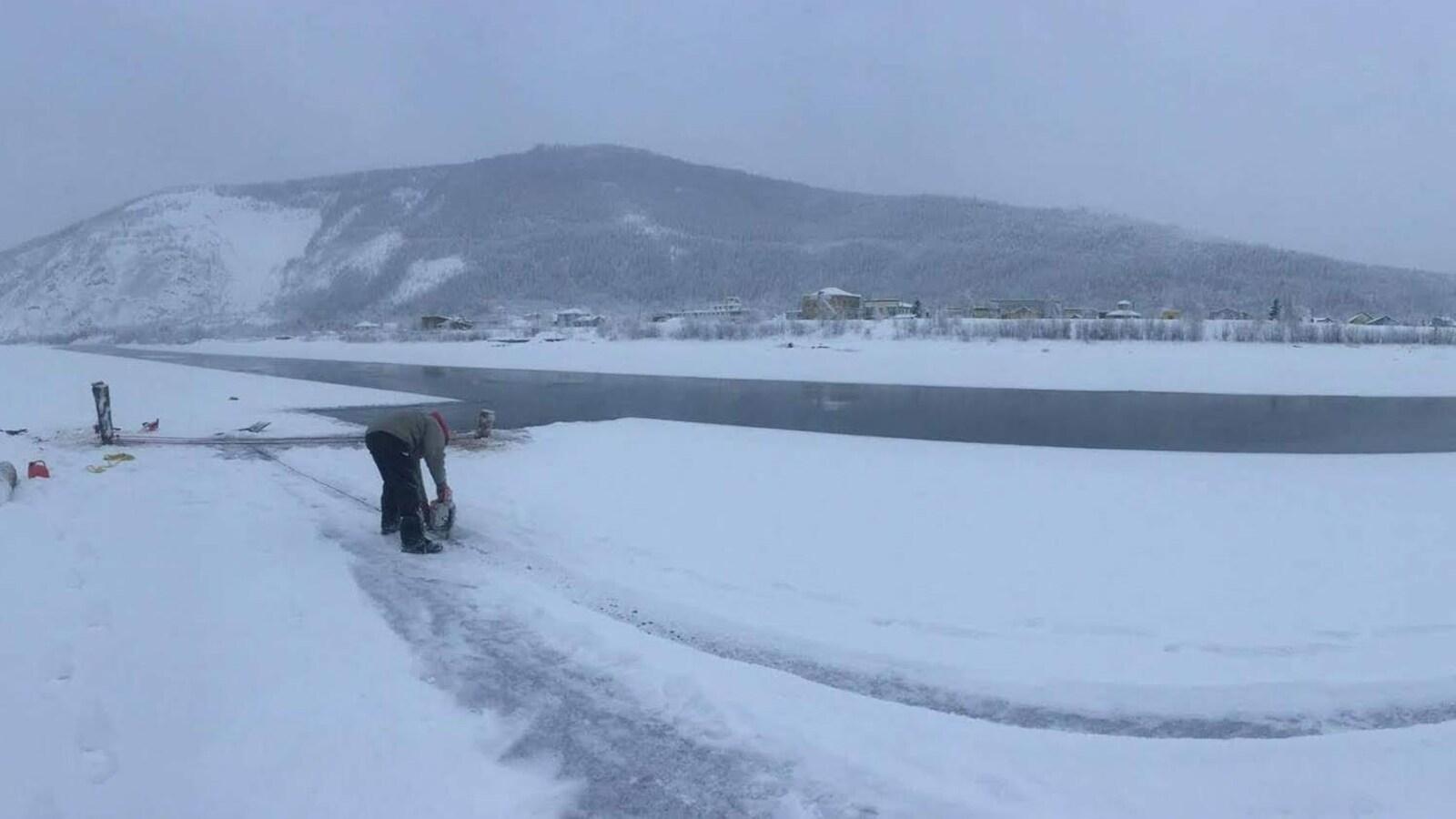 Un homme penché découpe de la glace dans l'eau.