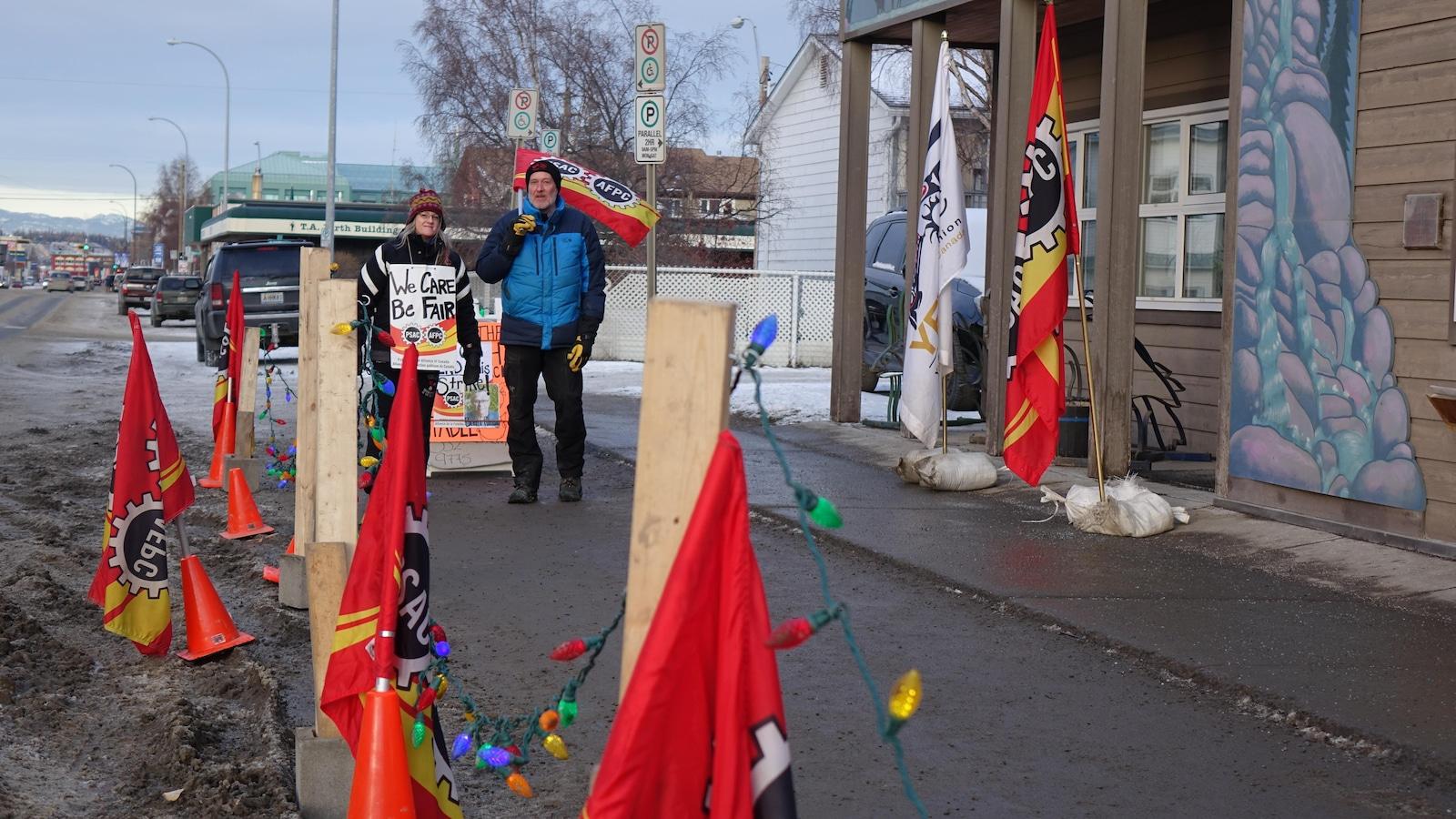 Une femme et un homme marchent sur la rue parmi des drapeaux devant un édifice.