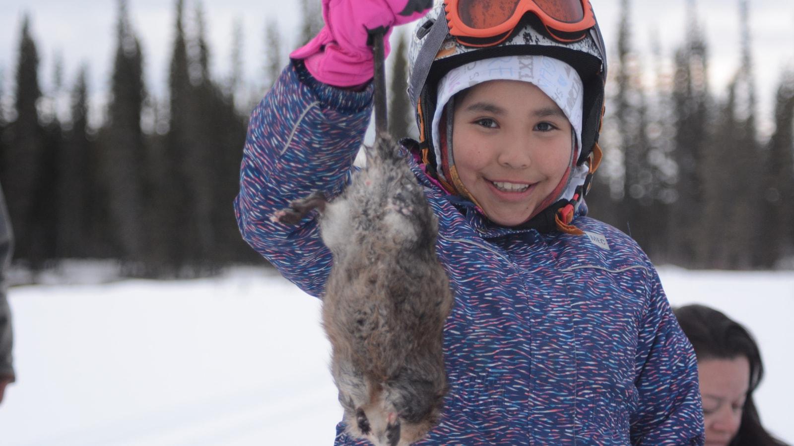 une fillette tient un rat musqué par la queue