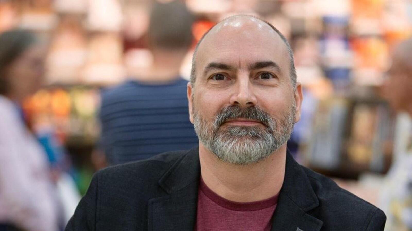 L'auteur Yvan Godbout photographié lors d'un salon du livre. On aperçoit, à l'avant-plan, une copie de son roman «Les Yeux jaunes».