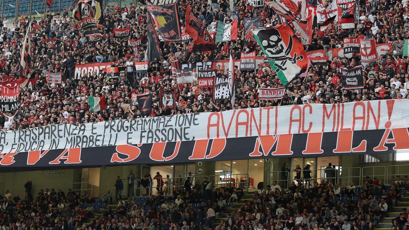Des partisans de l'AC Milan dans les gradins avec des banderoles et des drapeaux