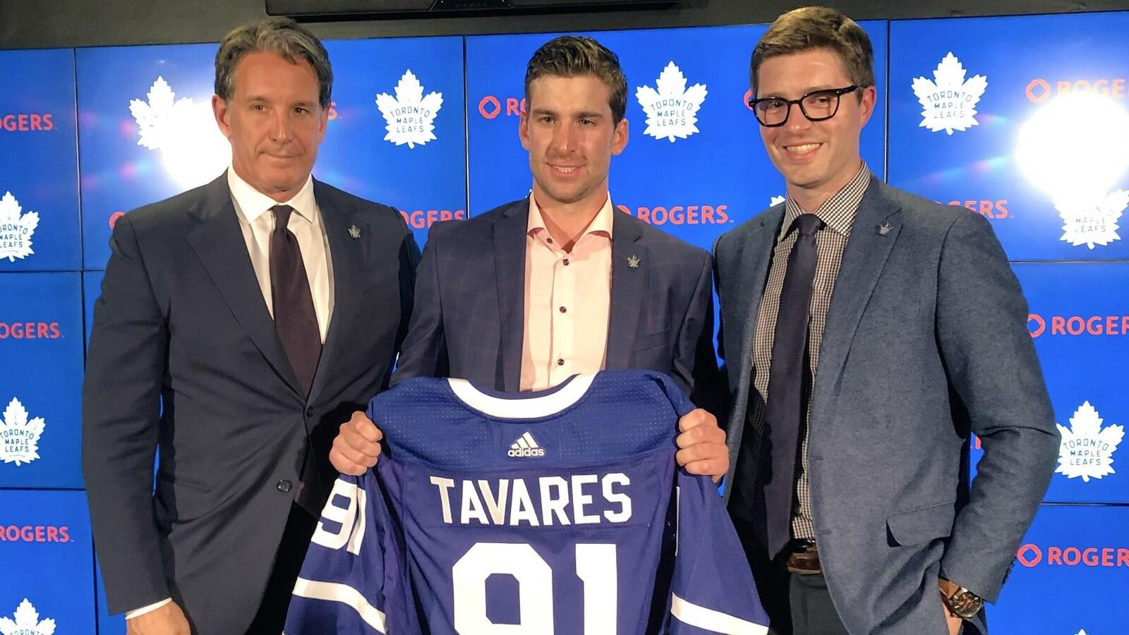 Entouré de Brendan Shanahan et Kyle Dubas, John Tavares tient dans ses mains un chandail des Maple Leafs de Toronto.