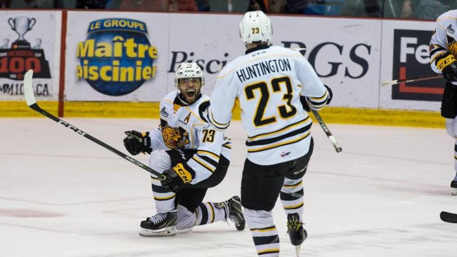 Deux joueurs des Tigres de Victoriaville célèbrent sur la patinoire après un but.