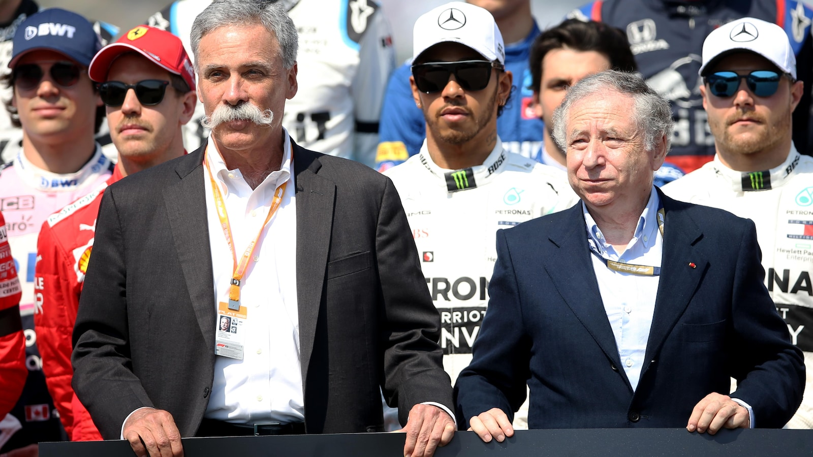 Chase Carey (à gauche) et Jean Todt sur la grille de départ du Grand Prix d'Australie, avec les pilotes dont Lance Stroll (casquette BWT) en arrière-plan
