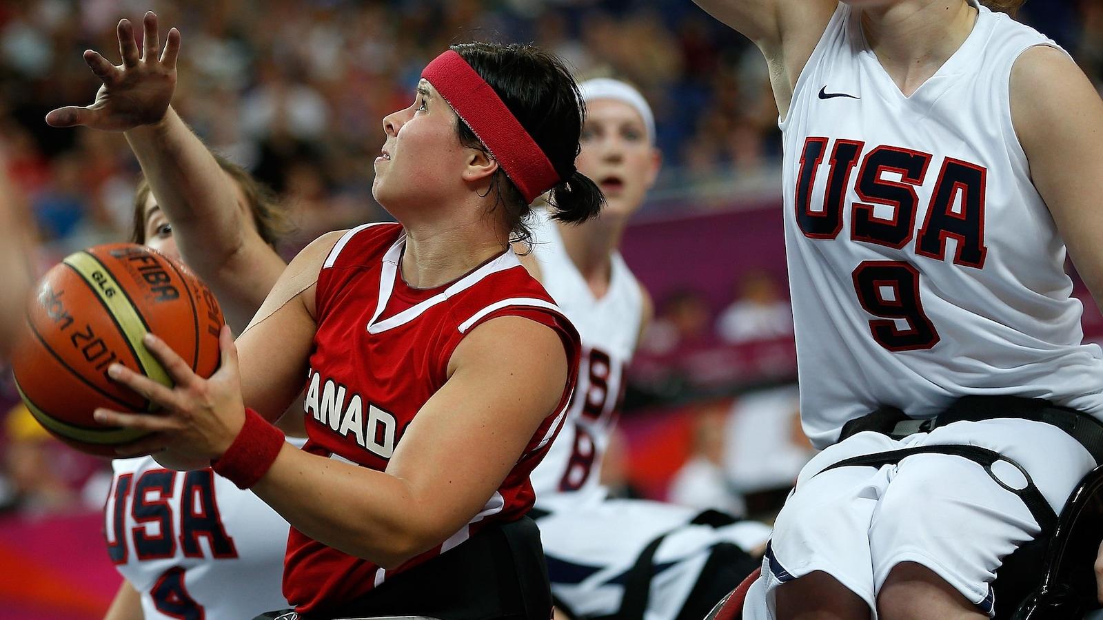 Cindy Ouellet, entourée de joueuses américaines, tente d'inscrire un panier.