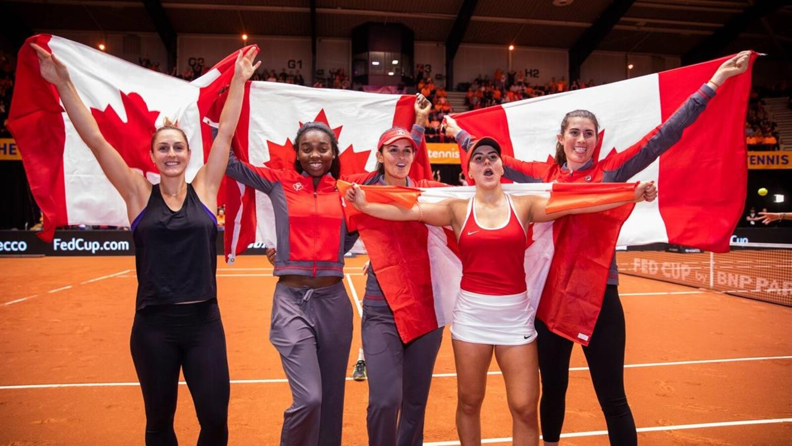 Les Canadiennes Gabriela Dabrowski, Heidi El Tabakh (capitaine), Françoise Abanda, Bianca Andreescu et Rebecca Marino célèbrent leur victoire contre les Pays-Bas avec des drapeaux canadiens alors qu'elles accèdent au barrage du groupe mondial, prévu les 20 et 21 avril prochains.