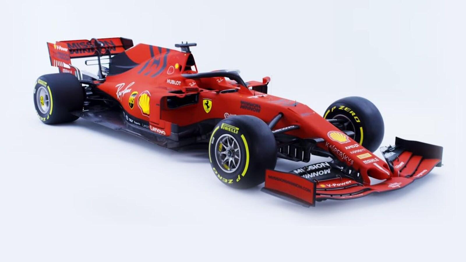 La voiture rouge est photographiée sur un fond bleu pâle.