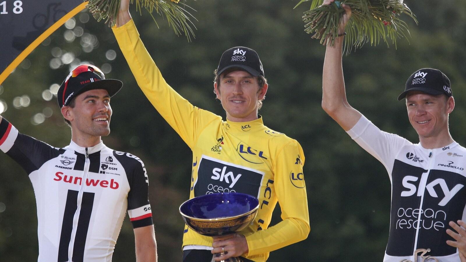 Il tient le trophée de la main gauche et des fleurs dans la droite.