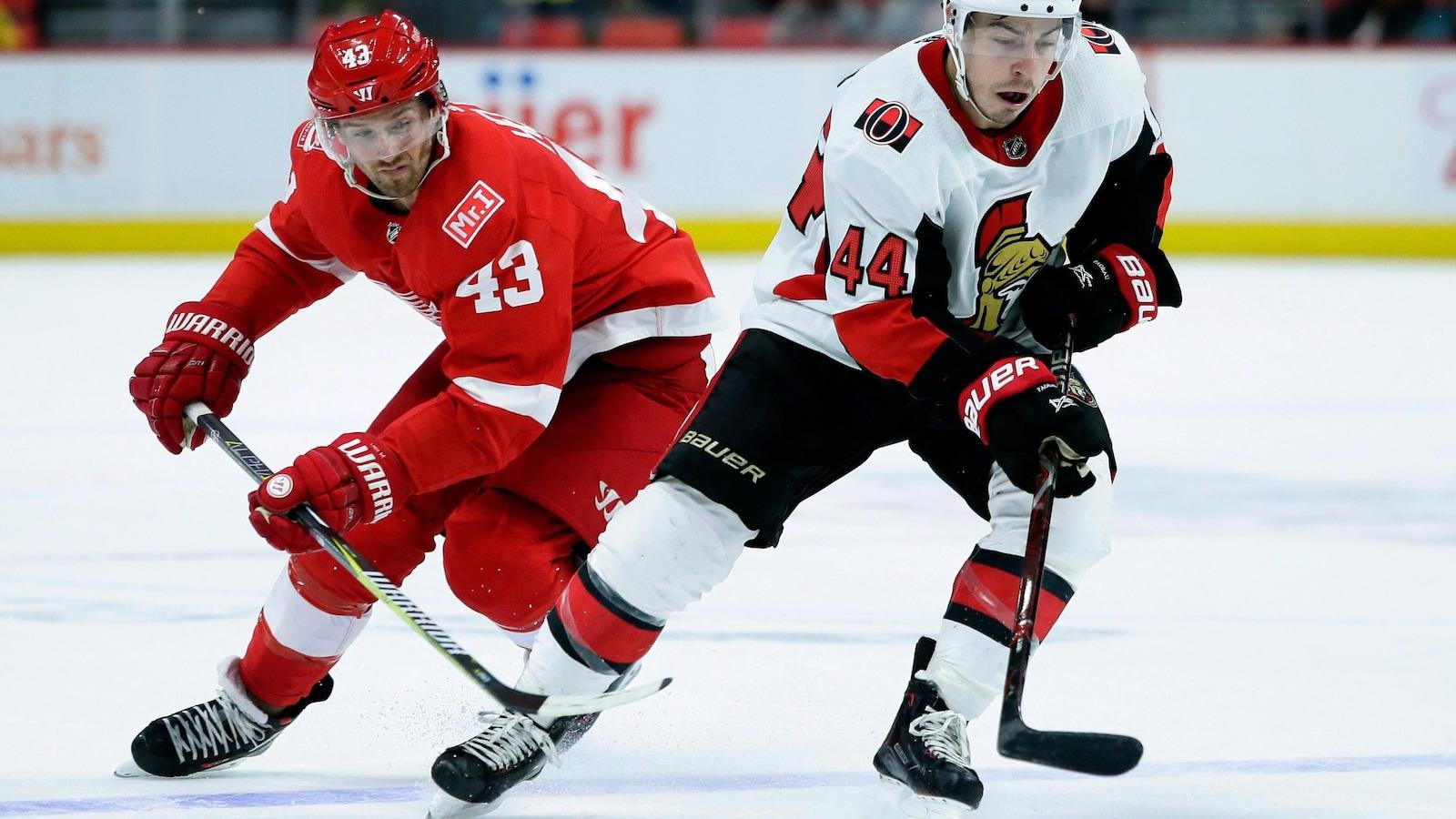 L'attaquant des Sénateurs d'Ottawa Jean-Gabriel Pageau vient de déjouer Darren Helm, des Red Wings de Détroit, durant un match.