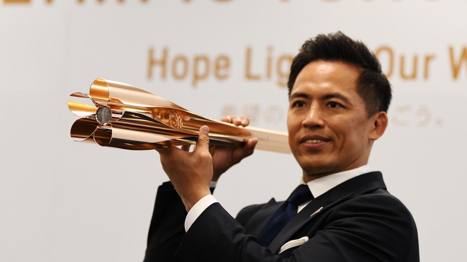 Tadahiro Nomura, triple champion olympique japonais de judo, présente le flambeau olympique des Jeux de Toyko.
