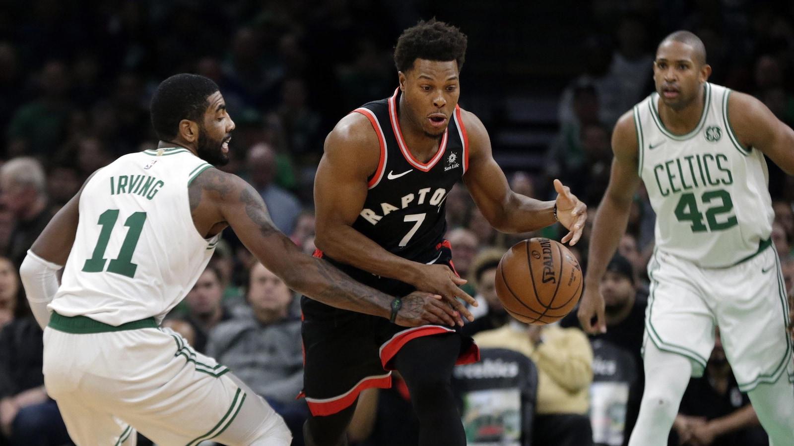 Le garde des Celtics Kyrie Irving vole le ballon à celui des Raptors Kyle Lowry, sous le regard de l'ailier fort Al Horford.