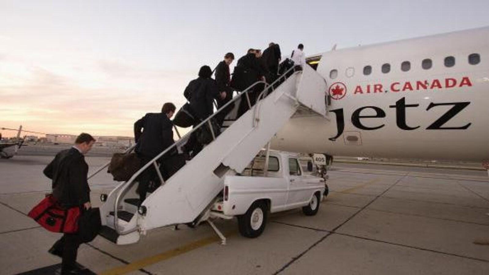 Des joueurs montent dans un avion d'Air Canada.