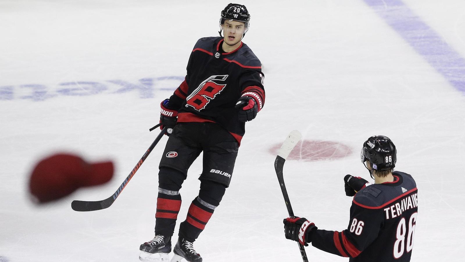 Sebastian Aho célèbre son troisième but du match avec Teuvo Teravainen, alors que la foule lance des chapeaux sur la glace.